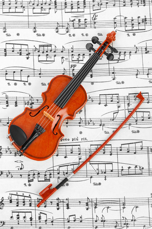 Toy violin and music sheet - art musical background photo
