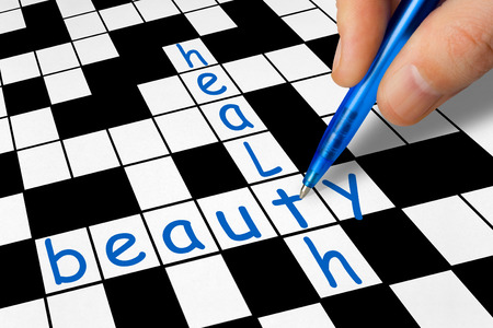 health answers: Hand filling in crossword - health and beauty