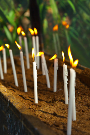 easter candle is burning: Candles on tomb at cemetery - religion background