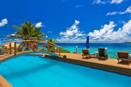 vacaciones en la playa: Piscina en la playa tropical - Seychelles - fondo de vacaciones