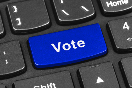 polling: Computer notebook keyboard with Vote key - technology background Stock Photo