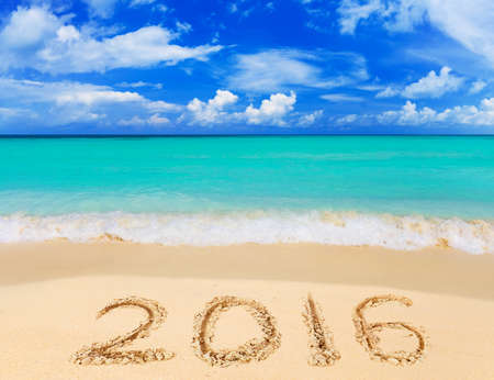 in the sand: Numbers 2016 on beach - concept holiday background