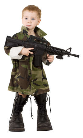 Full-length portrait of little boy with  automatic weapon in military boots and in camouflage jacket photo