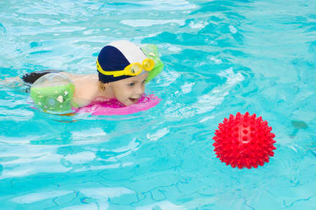 3 year old child playing with red ball in the swimming pool photo