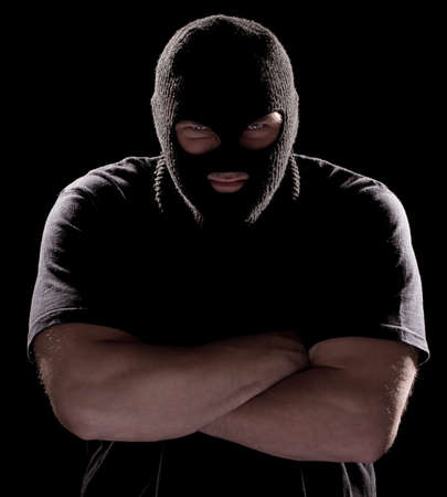 obscured:  Muscular burglar in mask, arms folded,  looking at camera from under eyebrows