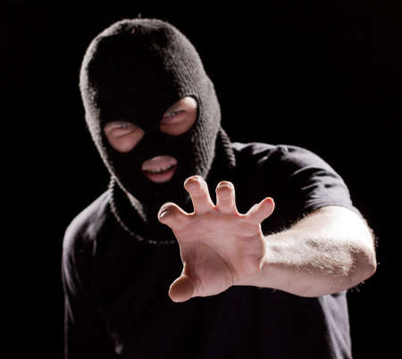 obscured face: Burglar in mask, robbing and catching something by hand