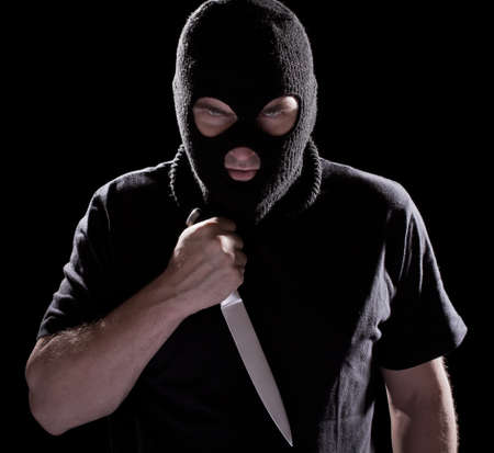 bandit: Burglar in mask holding knife on black background Stock Photo
