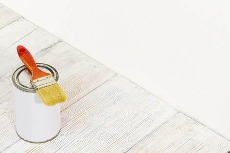 paint tin: Paintbrush and can, paint brush and white color container on wooden floor background
