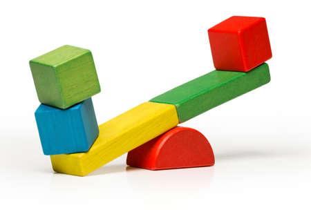 balanza: Balanc�n juguetes de bloques de madera, tambal�ese aisladas sobre fondo blanco cubo de contrapeso, swing con idea pesada y ligera