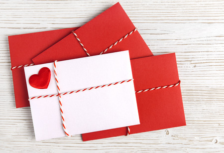 mail address: Envelope Mail with Red Heart and Ribbon over White Wooden Background. Valentine Day Card, Love or Wedding Greeting Concept.