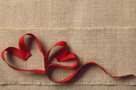 red ribbon bow: Two Hearts on Sackcloth Burlap Background. Valentine Day or Wedding Love Concept. Ribbon Shape as Joined Couple
