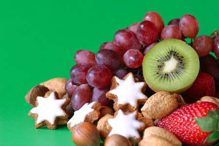 A selection of fruit, nuts and cookies with green background