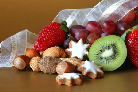 A selection of fruit, nuts and cookies on gold background photo