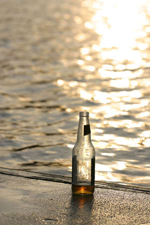 Evening at the waterfront with an almost empty bottle of beer.