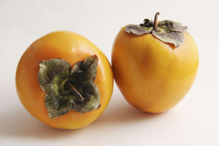 persimmons: Two persimmons on a white background. Stock Photo