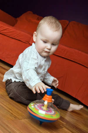 infancy: Cute caucasian baby boy (one year old) sitting on the floor and playing with his spinning top.