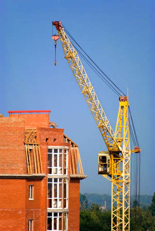 heave: The building crane stands near a builded house Stock Photo