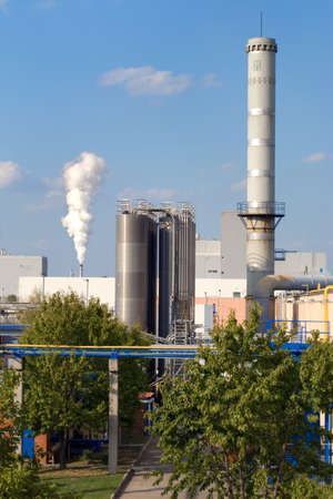energies: Factory pipes with a smoke on a background of the dark blue sky.
