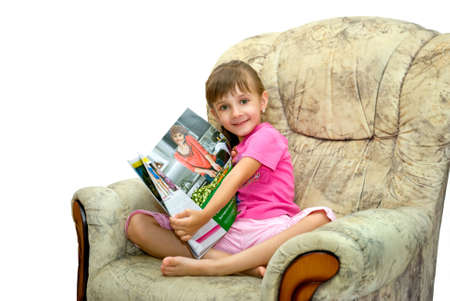 The girl sits in an armchair with magazine Stock Photo