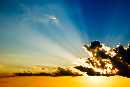Solar beams make the way through clouds on a decline  Stock Photo
