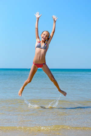 Child jumping at the beach, full of energy.