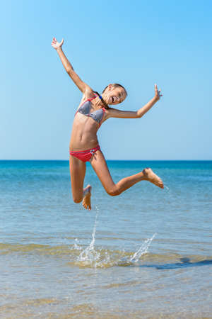 young girl bikini: Child jumping at the beach, full of energy.