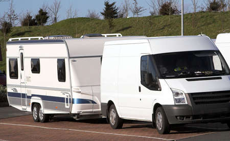 Touring caravan parked behind its towing vehicle on a parking lot