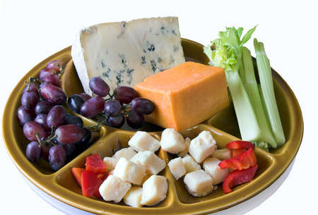 Platter with cheeses, grapes, peppers, and celery sitting on a white board Stock Photo
