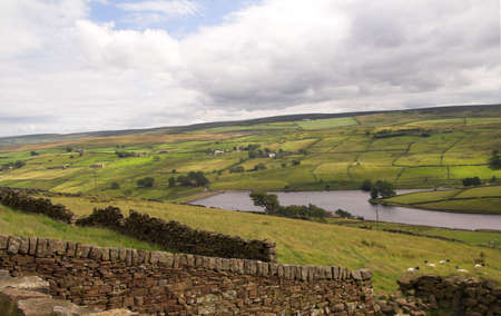 drystone: View across the Pennines, with a small tarn, drystone walls and lonely dwellings Stock Photo