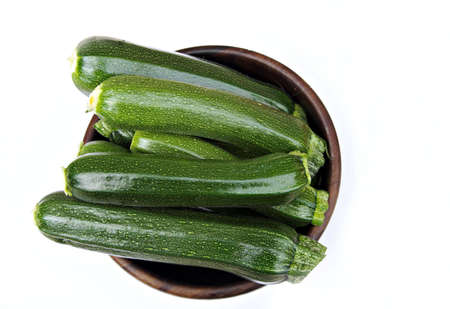 courgettes: Wooden bowl containing fresh cut courgettes, a.k.a. zucchini Stock Photo