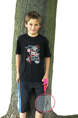 Boy with racquet and shuttle- standing against tree photo