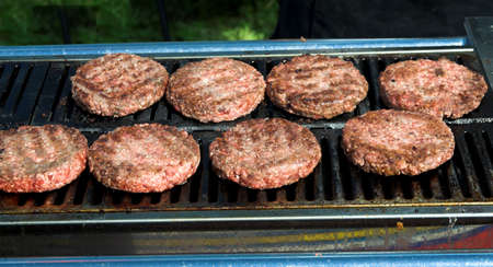 mincing: hamburgers starting to cook on a barbecue Stock Photo