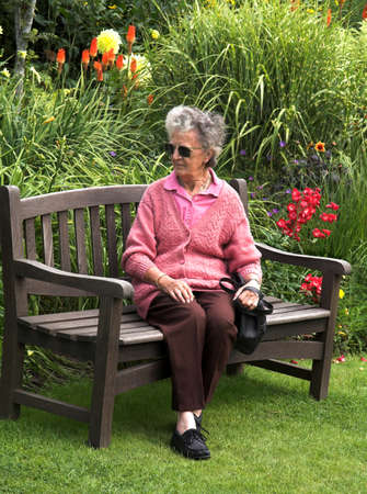 pokers: Elderly lady sitting on a bench amidst flowers and grasses