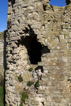 crumbling: Crumbling wall of ancient castle showing flint stones and a grill to prevent visitors from falling