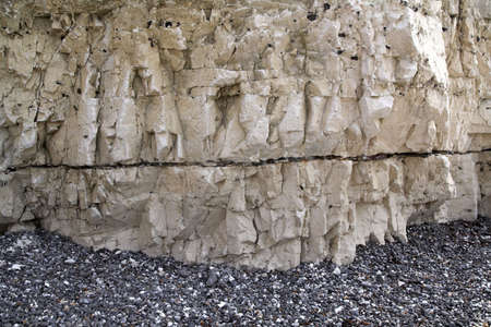 flint: Close-up of a chalk cliff with strata of flint and other stones