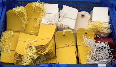 useful: Yellow and white luggage or parcel labels done up in bundles Stock Photo