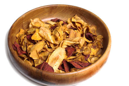 tans: Carved wooden bowl with crisps made from various root vegetables