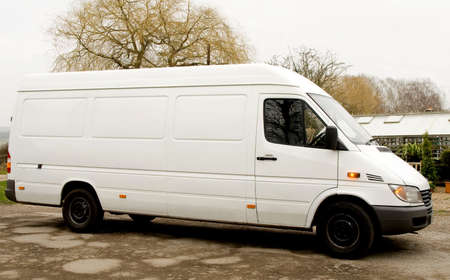 White Van with Indicators flashing parked by greenhouse