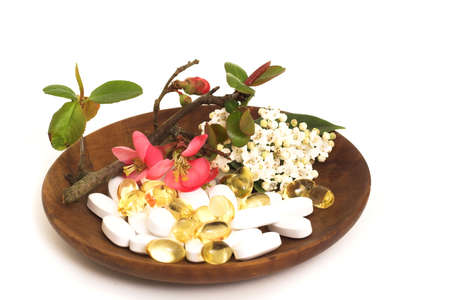 Various pills with japonica and lauristinus flowers on a wooden bowl Stock Photo - 2619068