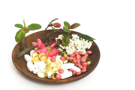 arious pills with japonica and lauristinus flowers on a wooden bowlarious pills with japonica and lauristinus flowers on a wooden bowl Stock Photo - 2619067