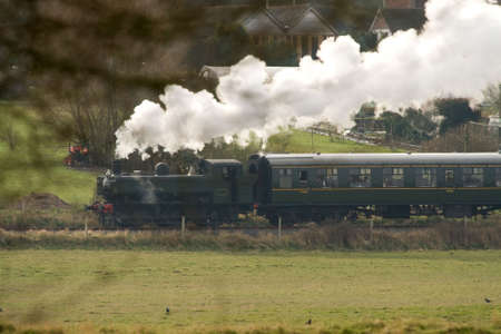 Old fashioned steam-train puffing through the countryside photo