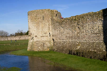 slits: Outer wall of ancient castle with surrounding moat Stock Photo