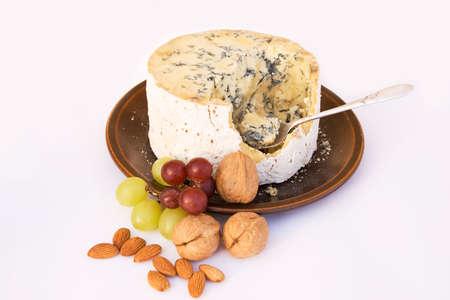 stilton: Stilton cheese, part eaten, with walnuts and grapes Stock Photo