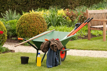 Wheelbarrow in a garden with clothes and a bottle of drink