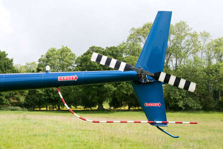 landed: tail rotor of a blue helicopter landed on a field
