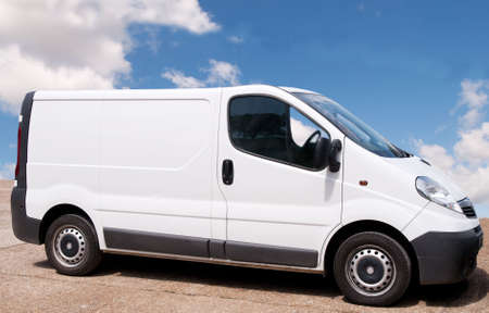 Small white trade-van parked on red forecourt