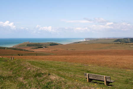 Empty seat with view across South Downs to the sea & cliffs photo