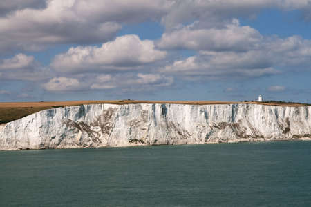 Light house perched on the White cliffs of Dover overlooking the sea Stock Photo
