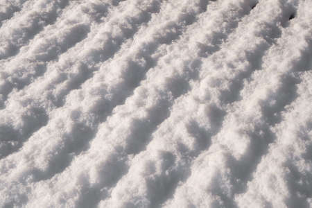 thawing: Snow melting from a slatted table top, more focused into the distance Stock Photo