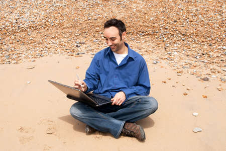 he laughs: Man laughs as he uses a quill with a laptop